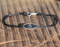 Silver Om Bracelet on waxed cotton